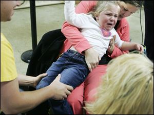 Matt Frey of Bowling Green and his wife, Jaimee, try to hold their daughter, Adrienne, 3, still so she can get a seasonal flu shot during a clinic administered by the Wood County Health Department. Adrienne was not exactly happy about getting a shot, even after watching her mom get one during the daylong clinic, held at the Wood County Fairgrounds in Bowling Green.