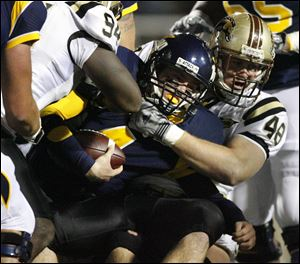 Toledo freshman quarterback Austin Dantin is tackled by WMU's Deauntay Legrier (94) and Justin Braska (48).