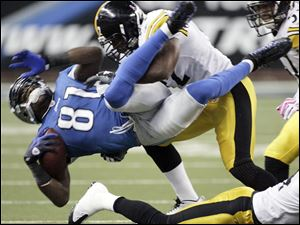 Detroit's Calvin Johnson is tackled by James Harrison. Johnson left the game in the first quarter with an injured knee.