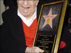 Soupy Sales poses for photographers with a replica, during a ceremony honoring him with a Star on the Hollywood Walk of Fame, in this January 7, 2005 file photo taken in Los Angeles. Sales, the rubber-faced comedian whose anything-for-a-chuckle career was built on 20,000 pies to the face and 5,000 live TV appearances across a half-century of laughs, died Thursday.
