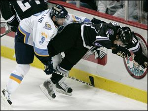 Toledo's Malcolm MacMillan knocks Reading's Jimmy Fraser to the ice during the first period Friday night at Lucas County Arena. The Walleye's record drops to 2-2-0. They play Trenton Saturday night.