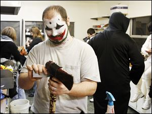 Andy Johnson of Walbridge prepares his ax for a night of scares at TerrorTown, where the budget for such props has been cut.