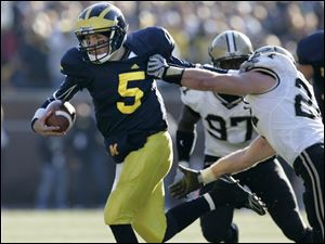 Michigan quarterback Tate Forcier breaks free of Purdue's Jason Werner in the fourth quarter. Forcier was sacked four times.