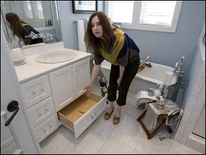 Subcontractor Amy Birdsong shows off a drawer built into the base of a vanity cabinet.