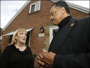 Toledoan Kimberly Bowers talks to the Rev. Jesse Jackson outside her home, which she could lose to foreclosure. A spokesman for her lender said the process has been placed on hold.