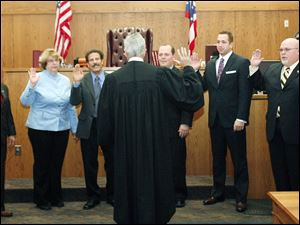 Slug: CTY oregon30p                       Date 11/29/2009           The Blade/ Amy E. Voigt                   Location: Oregon,  Ohio NOTE TO DESK: Mr. Peach was not there.  CAPTION:   Judge Jeffrey Keller of Oregon Muncipal Court, center, swears-in Oregon City Council members from left: Michael Sheehy,  Sandy Bihn, James Seaman, Dennis Walendzak, Clint Wasserman, and Terry Reeves during a ceremony on November 29, 2009.  There will be  a farewell luncheon and open house for Marge Brown, who was mayor of Oregon for eight years, at 12:30 p.m. Monday in City Council Chambers, 5330 Seaman Road.