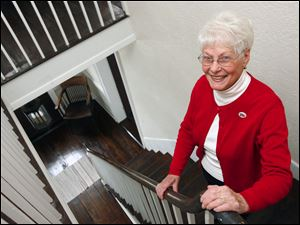 A staircase in the McPherson residence provides the backdrop for Pat Gill, president of the Clyde Heritage League. The group recently completed a $50,000 renovation of the home.