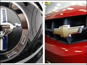In this combo made from file photos, the logo is shown on the back of a Ford Mustang at a dealership in Wexford, Pa., left, and a 2010 Chevy Camaro RS is shown on display at a dealership in Williamsville, N.Y. Ford is cranking up the horsepower on the 2011 Mustang as it tries to win back muscle car sales from its archrival, the Chevrolet Camaro. (AP File Photos)