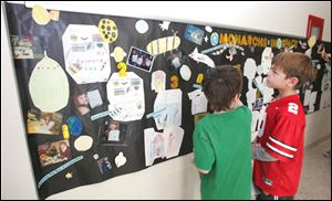 Devin Maynard, left, and Carson Webster check out the Monarchs in Space mural that Mrs. Herr's second-grade class created.