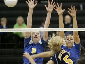 St. Ursula's Maggie Burnham, left, and Erin Williams try to block a shot by Notre Dame's Paige Roback. Burnham and Roback were both named to the All-City volleyball fi rst team.