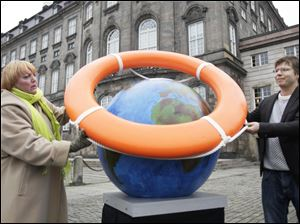 Claudia Roth, leader of Germany's Green Party, and Jakob Norhoj of the Danish Socialist People's Party place a life preserver around a globe near the parliament building in Copenhagen, the city where the climate-change summit is taking place. Representatives of 192 nations are seeking an agreement on how to address global warming.