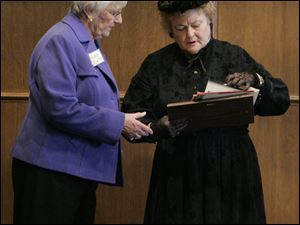Paula Miklovic, left, discusses details of the centennial luncheon at the Toledo Club with Patsy Johnson Gaines, who attended as the personification of Susan B. Anthony.