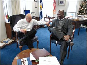 Toledo Mayor Carty Finkbeiner shares a laugh with his successor, Mike Bell, as the pair meet in the mayor's office on the 22nd floor of One Government Center. The two met yesterday morning to discuss the transition between the two administrations. Mr. Bell was elected in November and is to take the oath of office Monday. Mr. Finkbeiner did not seek re-election.