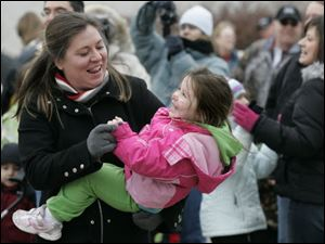 Kristy Weaver of Sylvania dances with her daughter, Ava, 3, as the ball ends its descent. Those attending the zoo's celebration could make a few ReZOOlutions to be a little greener in 2010, watch an ice carving demonstration, or make crafts.