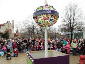 A crowd watches as the ball drops during the 'Happy Noon Year' celebration at the Toledo Zoo. Family friendly activities were featured at the event yesterday — held at noon so children could take part — and celebrants toasted the new year with apple juice.