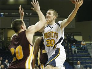 The Rockets' Jake Barnett puts up a shot over Central Michigan's Robbie Harman. Barnett was Toledo's high scorer with 19 points.