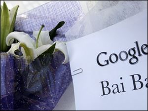 "A sign, which reads ""Google Bai Bai (bye bye)"" is seen near flowers, left by visitors outside the Google China headquarters in Beijing, Wednesday."