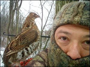 Pesky ruffed grouse sits on shoulder of Toledo hunter Eric Thompson while hunter and his son, Bradley, 13, waited in a treestand in southern Ohio.