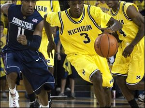 Michigan's Manny Harris streaks up the court while being pursued by Connecticut's Jerome Dyson.