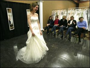 From left, Katie Lyons, Lisa Ritchie, Judy Lyons, Susan Skursha, and Lilian Homa, all family members, admire the bridal gown Jennifer Ritchie of Cleveland is modeling for her July nuptials. Ms. Ritchie shopped at the Brides against Breast Cancer Gown sale at The Pinnacle last weekend and said that although she spent more than she planned, it was worth it for the cause, not to mention the dress. All gowns were from top manufacturers and designers.