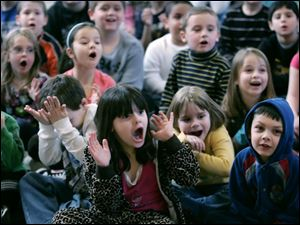 Students at Wayne Trail Elementary in Maumee, including Kristian Birr, 5, Monica DeGasto, 5, Sydney Ervin, 5, and Nicholas Johnstone, 6, from left in front, react in shock and wonderment as they watch a science demonstration at their school Thursday.