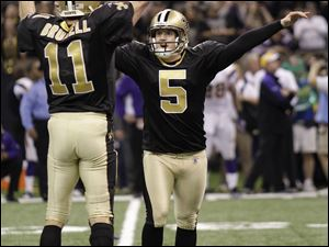 Garrett Hartley (5) of New Orleans celebrates with Mark Brunell after kicking the game-winning field goal to lift the Saints past Minnesota in overtime last night in the Superdome.