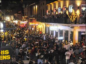 New Orleans fans flock to Bourbon Street to celebrate the Saints' 31-28 victory over the Minnesota Vikings in the NFC title game.