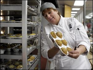 Kelley Bryan checks her muffins in a cooking class. She entered the school after spending three months looking for a job and deciding to retrain for a new career.