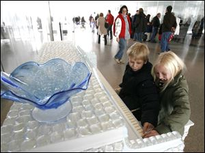 Sam Garner, 9, and his sister Sadie Garner, 7, of Holland, play a glass-covered piano at the Glass Pavilion. WinterFest continues next weekend with special offers and discounts offered.