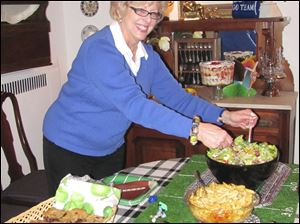 Marlene Uhler tosses a salad for guests at her Super Bowl party.