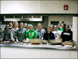 Members of the Ottawa Hills girls basketball team prepare to dish out the meal they prepared at the center.