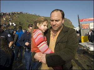 Vince Perrini carries his daughter, Sofia, away from the scene of mayhem as spectators were struck by rogue waves at a surfing contest in California. The father and daughter were swept into the sea by one wave.