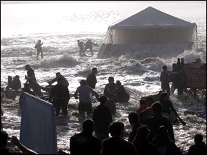 Spectators scramble after giant rogue waves hit the beach during the Mavericks surfing contest at Pillar Point, Calif., near Half Moon Bay. At least 15 people were hurt seriously.