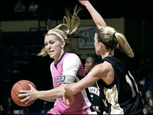 UT's Lisa Johnson drives on Western Michigan's Molly Dwyer Saturday at Savage Arena. After the game, UT's pink uniforms were auctioned, with a few of the jerseys collecting $1,000 or more from bidders to fight cancer.