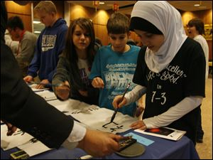 Springfield Middle School students, from right, Zainab Hussein, Andrew Jacobs, Tiffany Osborn, and Ben Baumgartner practice Chinese calligraphy at the Chinese Lantern Festival Carnival at the University of Toledo. Yesterday's event on Chinese culture was sponsored by the Confucius Institute at UT.