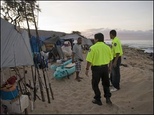 Officers with the Hawaii Department of Emergency Management notify homeless campers on Maile Beach in Waianae, Hawaii, of the tsunami warning.