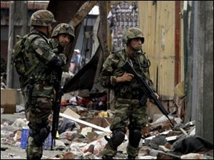 Soldiers stand guard in the streets of Talcahuano, Chile, Sunday, Feb. 28, 2010. A devastating earthquake struck Chile early Saturday Feb. 27, 2010 knocking out power and closing most businesses.
