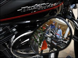 Slug: CTY harley01p Date:  02282010     Andy Morrison       Location: Toledo  Caption: Wayne Smith and Jan Gibson, Holland, are reflected in a mirror as they check out the bikes on display at Westfield Franklin Park Mall at the Toledo Harley Owners Group, Chapter 1524's 17th Annual Motorcycle Show and Raffle, Sunday, 02282010. Summary.