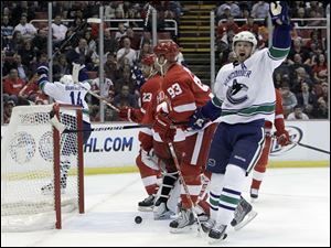 Vancouver's Henrik Sedin celebrates a first-period goal by Alexandre Burrow, left, against Detroit in last night's game.