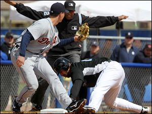 Toronto's Jose Bautista, right, slides safely under the tag of Detroit's Brent Dlugach during the Tigers' spring training opener.