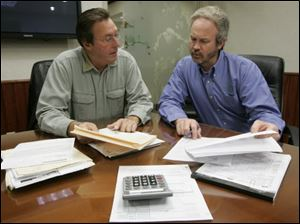 David Friedman, a retired doctor, left, goes over his paperwork with Steve Schult, a tax partner with Gilmore, Jasion & Mahler Ltd., at the certified public accounting firm's offices in Maumee.
