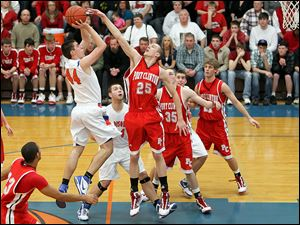 Port Clinton's Ryan HIcks tries to block a shot by of Edison's Ryan Reber. Hicks, a 6-foot-6 senior,