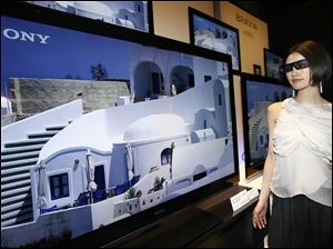 Sony Corp's 3-D televisions are introduced as a model watches with 3-D glasses in Tokyo. The company plans to start selling the sets in June, joining an industry push for consumers to buy the sets.