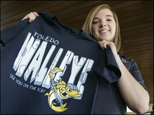 Notre Dame senior Sarah Kobylak of Rossford, left, holds her winning design for the Walleye T-shirt.