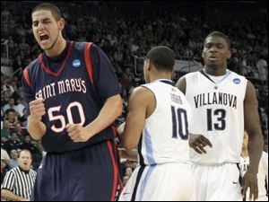 Saint Mary's Omar Samhan (50) celebrates in front of Villanova's Corey Fisher (10) and Mouphtaou Yarou in the second half.