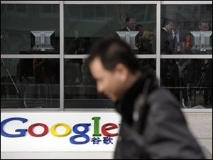 A security guard walks past while foreign visitors are seen inside the Google China headquarters in Beijing Tuesday, March 23, 2010. Google Inc. stopped censoring the Internet for China by shifting its search engine off the mainland Monday but said it will maintain other operations in the country. The maneuver attempts to balance Google's disdain for China's Internet rules with the company's desire to profit from an explosively growing market.