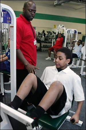 Corey Allison shows TPS student Daquan Jordan, 13, how to use workout equipment at the Wayman D. Palmer Community YMCA on North 14th Street. The initiative includes free transportation for students on TARTA buses from their schools to the partner YMCAs.