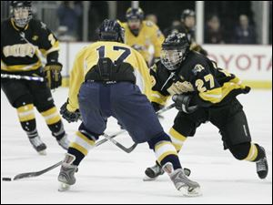 Northview's Zach Felser (27) sweeps the puck past a  Cleveland St. Ignatius player during the championship game.