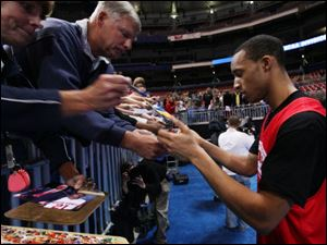 Ohio State's Evan Turner signs autographs after a practice session in St. Louis.