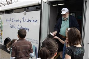 Librarian John Powell assists students during a stop at Eastpointe on the Mall apartments in Northwood.
